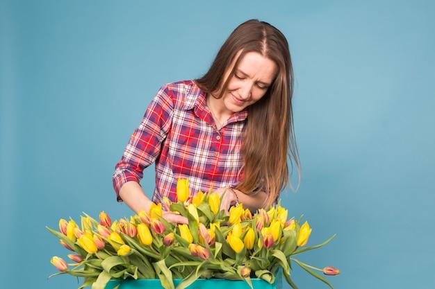Vrolijke jonge vrouwenbloemist met doos van tulpen over blauwe achtergrond