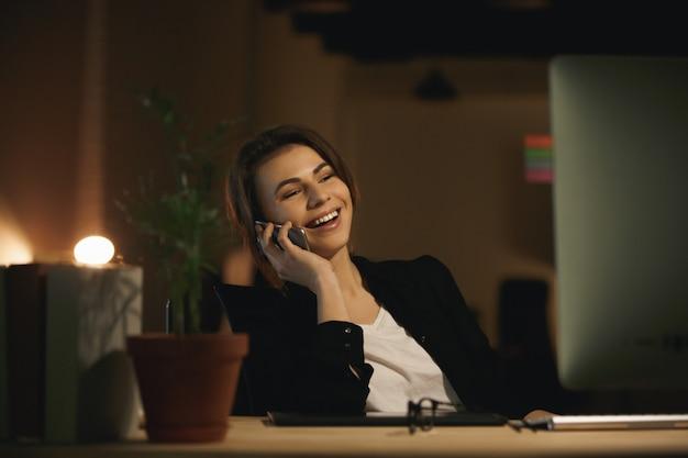 Vrolijke jonge vrouwenontwerper die telefonisch spreekt