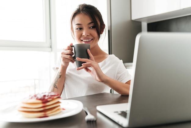 Vrolijke jonge vrouwenzitting bij de keuken die laptop met behulp van