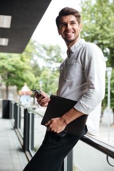 Vrolijke jonge zakenman die map vasthoudt en mobiele telefoon buitenshuis gebruikt