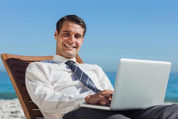Vrolijke jonge zakenman die op een ligstoel met zijn computer ligt