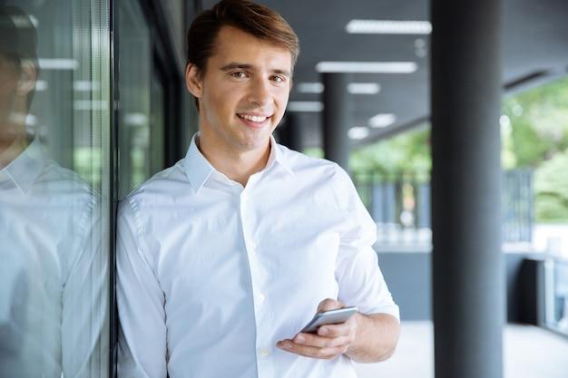Vrolijke jonge zakenman laptop houden en praten op mobiele telefoon in de buurt van zakencentrum