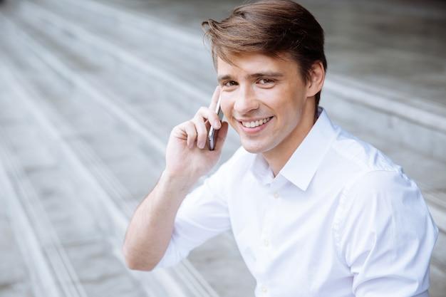 Vrolijke jonge zakenman met behulp van smartphone in de buurt van zakencentrum