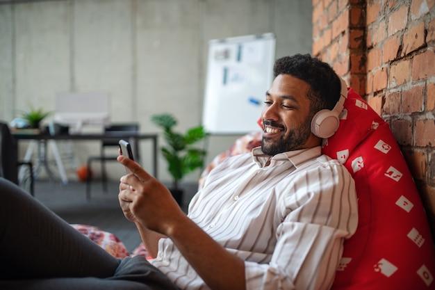 Vrolijke jonge zakenman met koptelefoon en smartphone in kantoor, een pauze nemen en ontspannen.