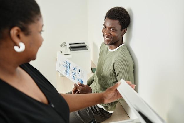Vrolijke jonge zakenman met rapport in de hand in gesprek met vrouwelijke collega die kopieën maakt van d...