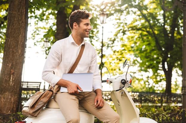 Vrolijke jonge zakenman zittend op een motor buitenshuis, met laptopcomputer