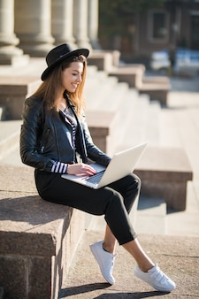 Vrolijke jonge zakenvrouw student meisje werkt met haar merk laptopcomputer in het stadscentrum