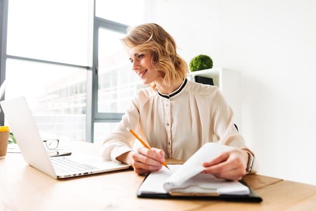 Vrolijke jonge zakenvrouw zitten in kantoor