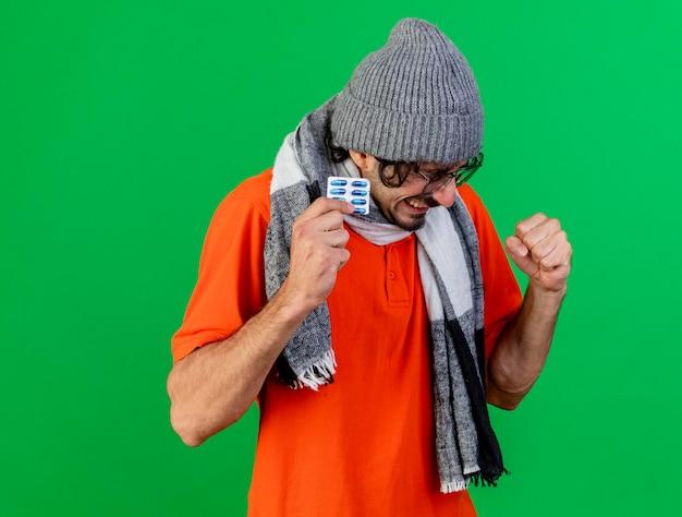 Vrolijke jonge zieke man met bril, muts en sjaal bedrijf pack van medische capsules ja gebaar geïsoleerd op groene muur met kopie ruimte te doen