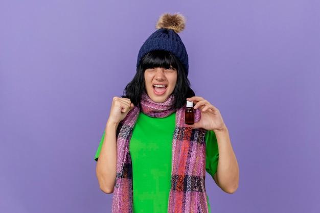 Vrolijke jonge zieke vrouw die de wintermuts en sjaal draagt die medicijn in glas houdt die kant bekijkt die ja gebaar doet dat op purpere muur met exemplaarruimte wordt geïsoleerd Gratis Foto