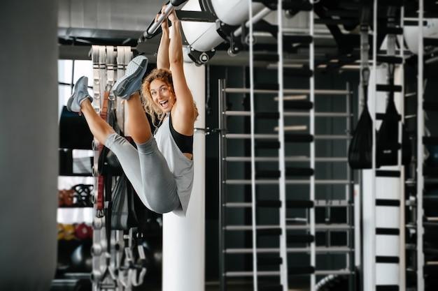 Vrolijke jongedame die fitness doet op de muurbars van de apparatuur in de sportschool en buikspieren trainen