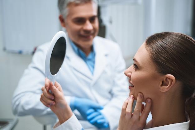 Vrolijke jongedame geniet van haar glimlachreflectie terwijl ze in een stoel zit in de buurt van mannelijke tandarts
