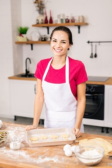 Vrolijke jongedame in schort op zoek naar jou tijdens het bereiden van lekkere koekjes door tafel in de keuken