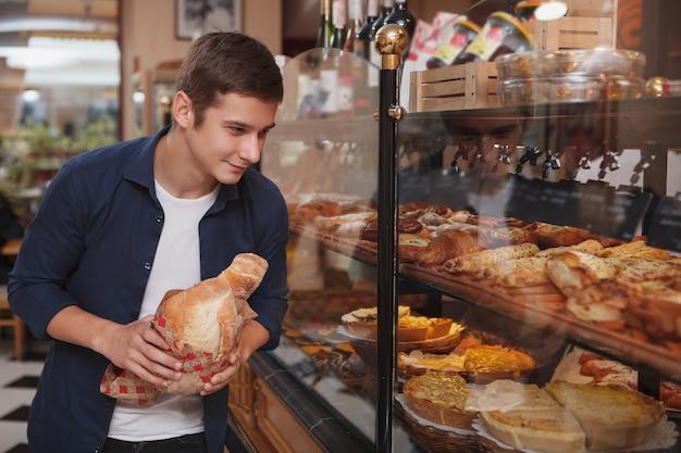 Vrolijke jongeman brood en gebak kopen bij lokale bakkerij, kopie ruimte
