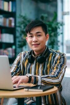 Vrolijke jongeman die aan tafel zit met een laptop erop en er blij uitziet