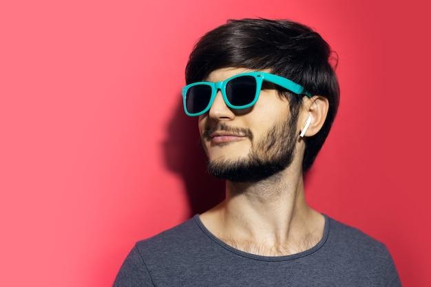 Vrolijke jongeman, die een cyaan zonnebril draagt en draadloze oortelefoons gebruikt op koraalroze muur.