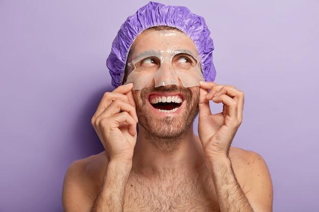 Vrolijke jongeman draagt een vochtinbrengend masker, een douchemuts, staat naakt binnen, heeft een vrolijke uitdrukking, houdt van schoonheidsprocedures