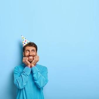 Vrolijke jongeman draagt papieren hoed en blauwe trui, heeft plezier op nieuwjaarsfeest