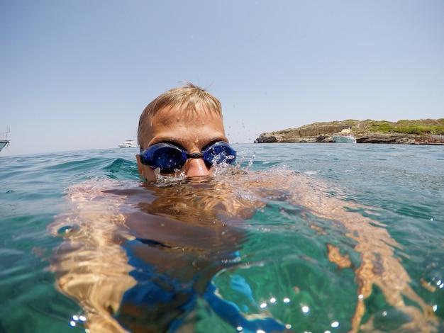 Vrolijke jongeman duiker zwemmen in de zee met bril in de buurt van kustlijn en jachten in zomervakantie.