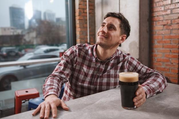 Vrolijke jongeman glimlachen, tv kijken in biercafé, kopie ruimte