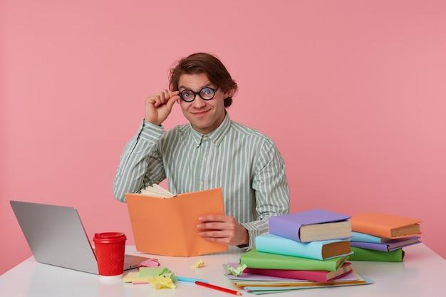 Vrolijke jongeman in bril draagt in shirt, zit bij de tafel en boek leest, kijkt naar de camera door een bril, werken met laptop, voorbereid voor examen, geïsoleerd op roze achtergrond.