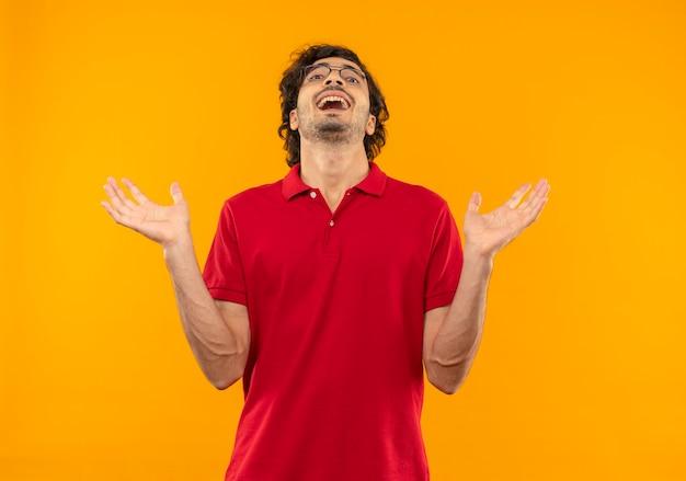 Vrolijke jongeman in rood shirt met optische bril houdt handen open en kijkt geïsoleerd op oranje muur