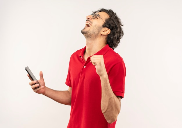 Vrolijke jongeman in rood shirt met optische bril houdt telefoon vast en steekt vuist omhoog geïsoleerd op witte muur