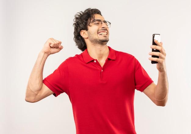 Vrolijke jongeman in rood shirt met optische bril kijkt naar telefoon en steekt vuist omhoog geïsoleerd op een witte muur