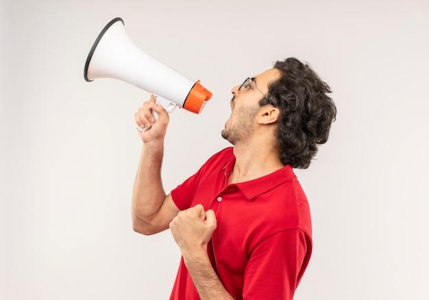 Vrolijke jongeman in rood shirt met optische bril schreeuwt via luidspreker en kijkt naar kant geïsoleerd op een witte muur