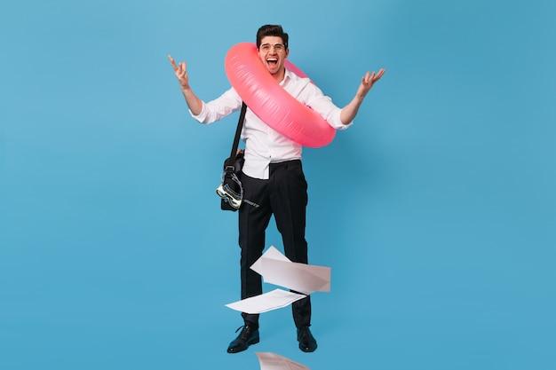 Vrolijke jongeman in wit overhemd en zwarte broek vormt met duikbril en roze rubberen ring. beambte gooide documenten weg.
