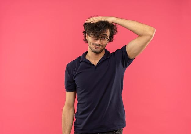 Vrolijke jongeman in zwart shirt met optische bril legt hand op het hoofd en kijkt geïsoleerd op roze muur