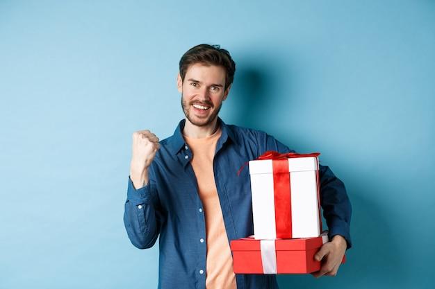 Vrolijke jongeman kreeg kortingen op valentijnsdag, vuist pomp maken en ja zeggen, geschenkdozen met cadeautjes voor minnaar vasthoudend, staande over blauwe achtergrond.