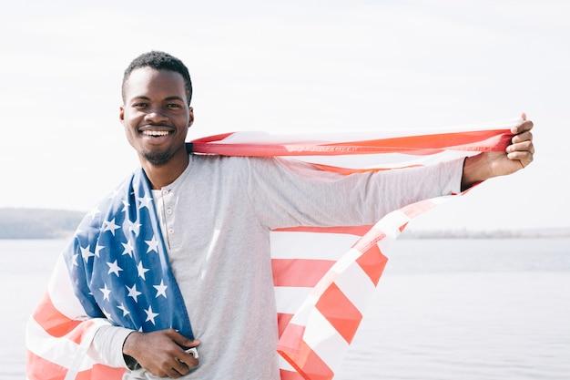Vrolijke jongeman met de vlag van de vs