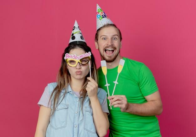 Vrolijke jongeman met feestmuts houdt nep-champagneglazen op stok en tevreden jong meisje houdt oogmasker op stok geïsoleerd op roze muur