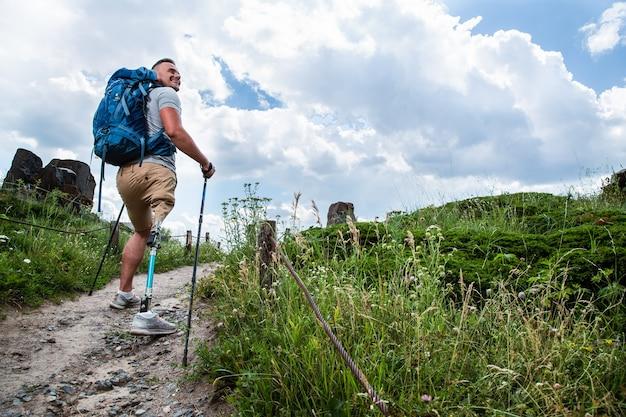 Vrolijke jongeman met prothese die nordic walking-lessen krijgt terwijl hij zich buiten gelukkig voelt