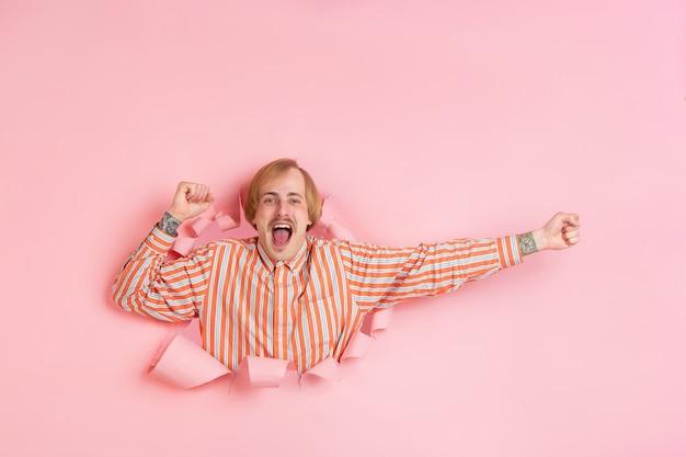 Vrolijke jongeman poseert in een gescheurde muur van koraalpapier, emotioneel en expressief