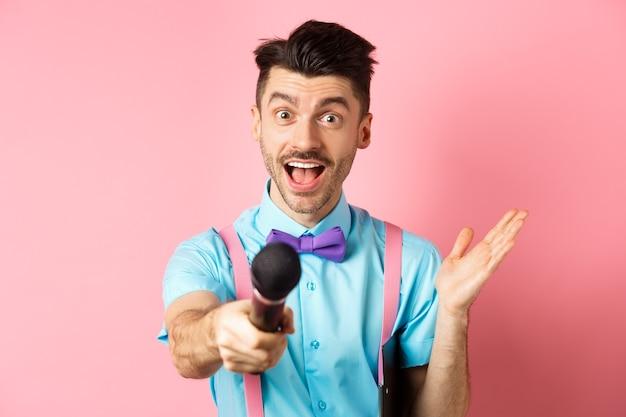 Vrolijke jongeman, presentator in vlinderdas die je microfoon geeft en glimlacht, mensen entertainen op feestelijke evenementen, optreden tijdens vakanties, staande op roze achtergrond.