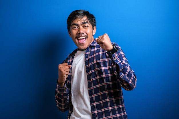 Vrolijke jongeman student in vrijetijdskleding geïsoleerd op blauwe achtergrond studio hief zijn arm op om zijn overwinning te vieren