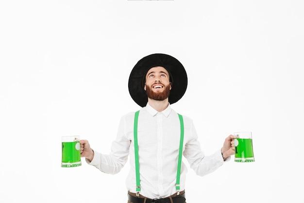 Vrolijke jongeman vieren stpatrick's day geïsoleerd over witte muur, bier drinken