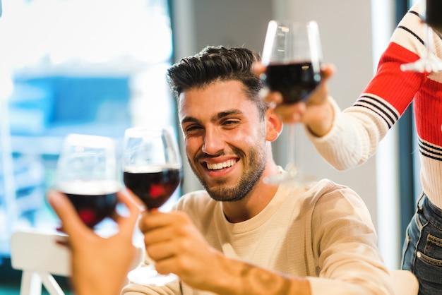 Vrolijke jongeman viert feest met vrienden die roosteren met een glas rode wijn terwijl ze hun wijnglazen opheffen in aanhef met focus op zijn gezicht