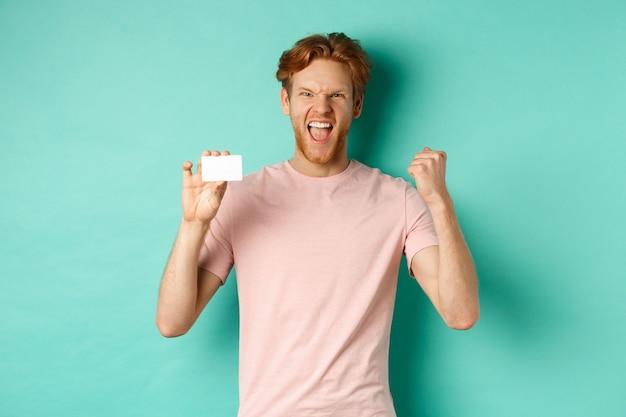 Vrolijke jongeman zegevierend, vuistpomp maken om succes te vieren, plastic creditcard tonen, prijs winnen van bank, turkooizen achtergrond.