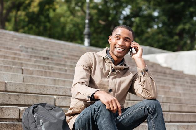 Vrolijke jongeman zittend op de trap tijdens het praten over zijn telefoon