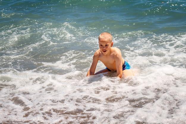 Vrolijke jongen baadt in de golven van de zee