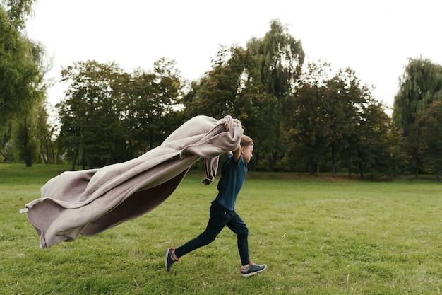 Vrolijke jongen die met een vliegende deken in het park loopt