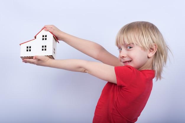 Vrolijke jongen die modelhuis houdt en lacht. portret van kind met stuk speelgoed huis in handen op witte achtergrond.