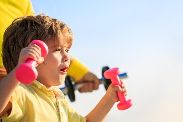 Vrolijke jongen doet oefeningen met halters. kind trainen met halters