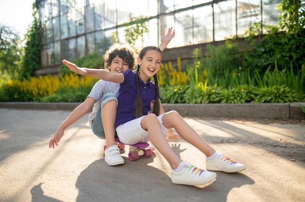 Vrolijke jongen en meisje zittend op skateboard in park