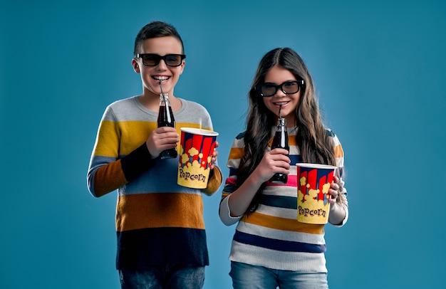 Vrolijke jongen en schattig meisje drinken een zoete koolzuurhoudende drank en eten popcorn in 3d-bril, op het punt om een film te kijken die op een blauwe achtergrond wordt geïsoleerd.