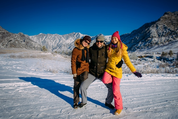 Vrolijke jongen en twee mooie meisjes poseren in kleurrijke winterkleren