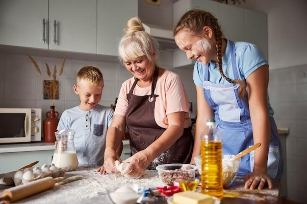 Vrolijke jongen en vrolijk meisje kijken hoe hun oma deeg maakt